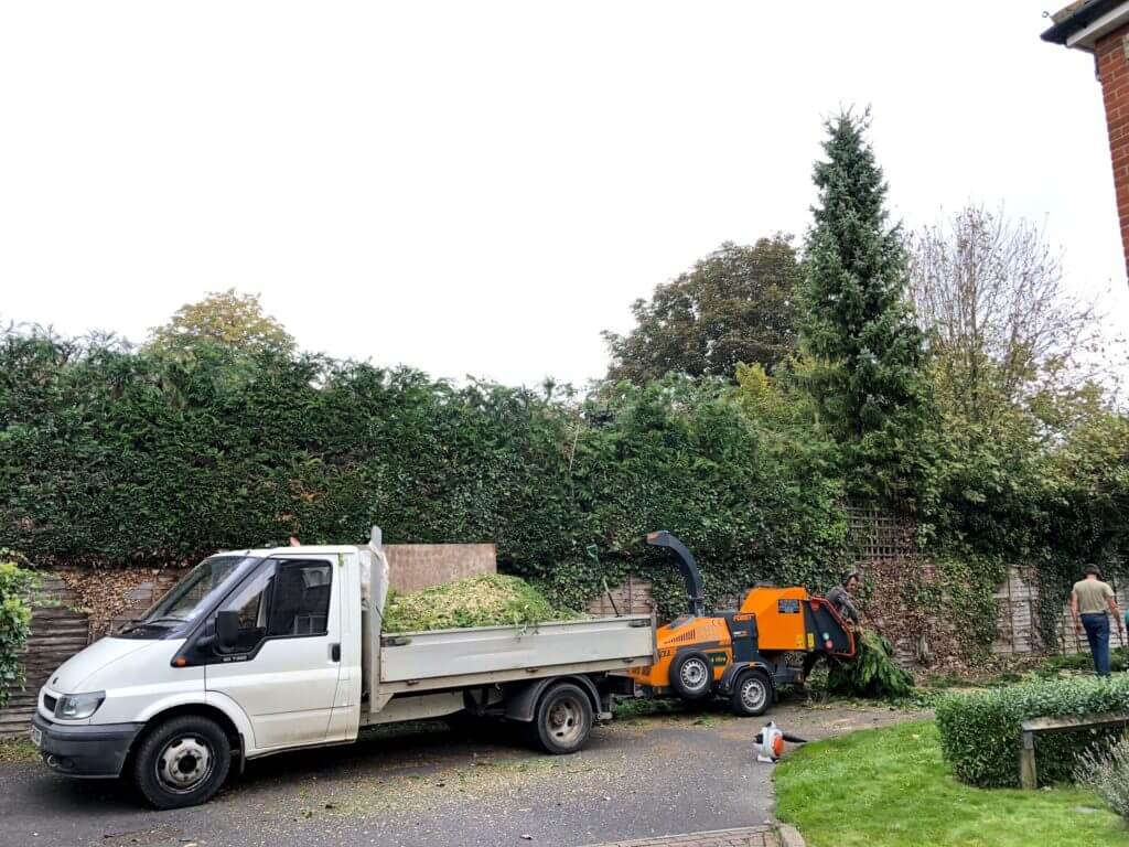 hedges being chipped with a grinder and van